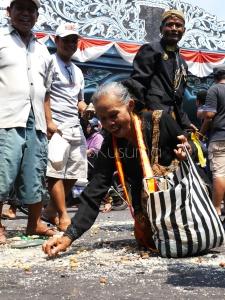 Seorang wanita bersemangat mengumpulkan remah gunungan dalam acara Gerebeg Syawal di depan Keraton Kasunanan Surakarta, Jawa Tengah. Acara ini menjadi salah satu acara yang diminati wisatawan setiap tahun.